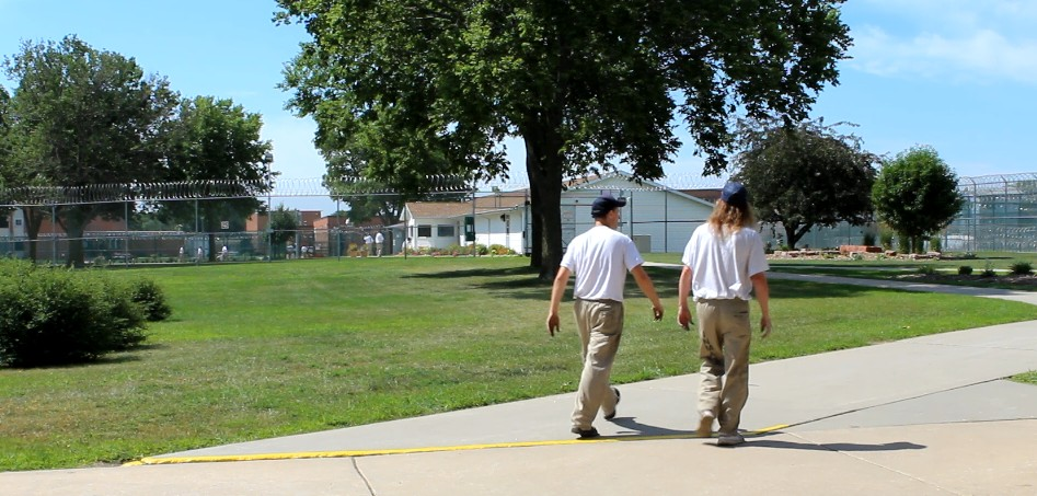 Inmates walk across the campus from their work site to the housing units.