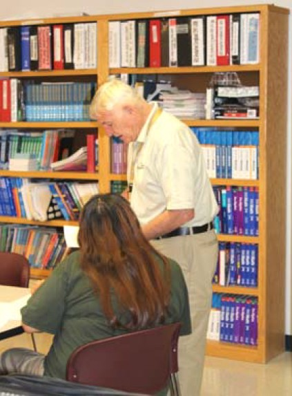 A teacher works with an inmate on her GED coursework.