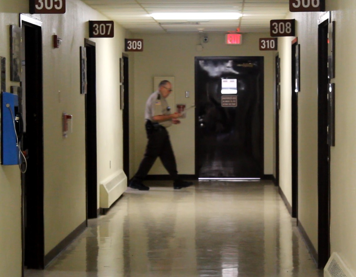 An officer makes rounds during a count of inmates.