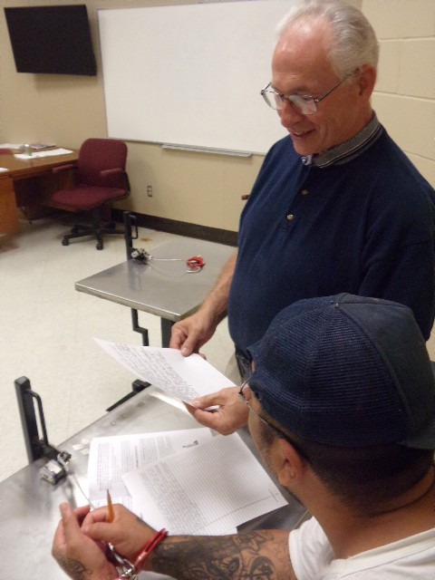A teacher reviews work completed by an inmate in Restrictive Housing.