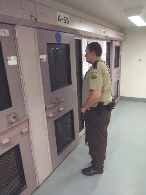 An officer talks with an inmate cell-front.