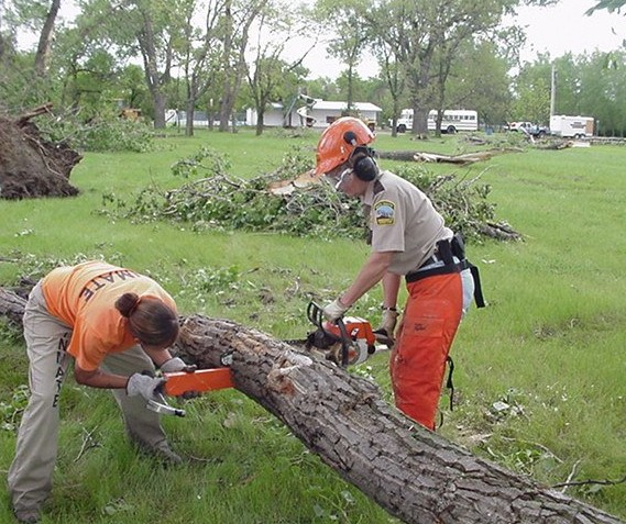 Female inmates trained to operate chain saws help clear debris in Lebanon, SD.