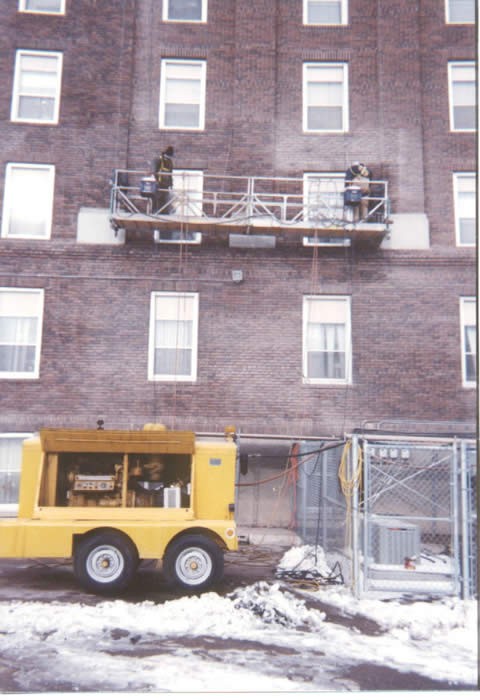 Inmates work on tuckpointing a state building.